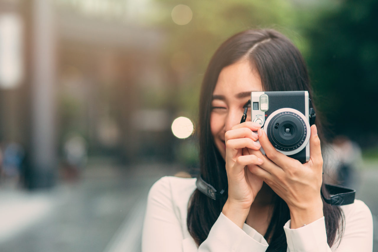 Portrait of a beautiful japanese woman taking a picture with a vinatage camera.